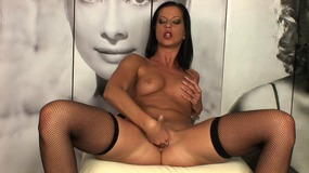 Stunning brunette plays with her pussy in the room wallpapered with huge portraits of cinema stars
