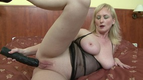 Blonde slut blows a long black dong and fucks it in bed